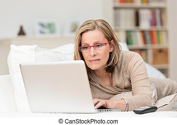Woman concentrating as she works on a laptop - Woman wearing...