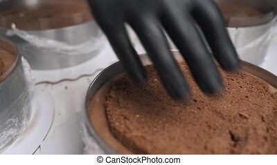 Woman confectioner in black uniform prepare cream for chocolate mousse cake. Stage cooking mousse cake