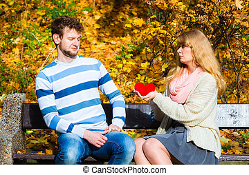 Confessing love and affection with romantic gesture. Rejection and disapproval. Negative reaction. Pair sit on bench in park woman hold plush heart showing her emotions man refuse.