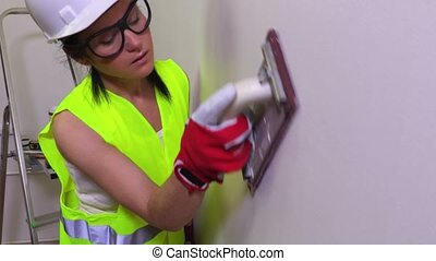 Woman construction worker grind the wall