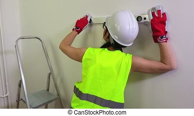 Woman construction worker using spirit level