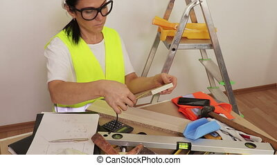 Woman construction worker using tape measure