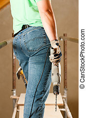Woman Construction worker with hand drill