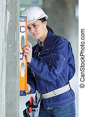 woman construction worker with level