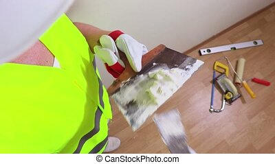 Woman construction worker with spatula near wall