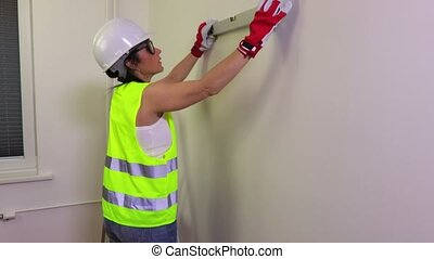 Woman construction worker with spirit level near wall