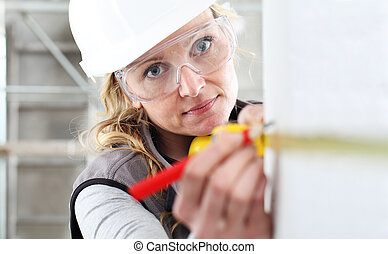 woman construction worker work with meter tape and pencil, measure wall in interior building site, wearing helmet, glasses and hearing protection headphones
