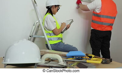 Woman construction worker writing near wall