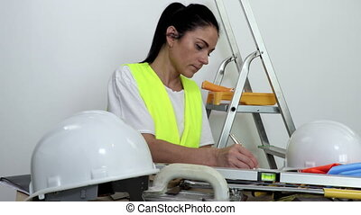 Woman construction worker writing