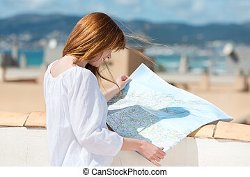 Woman consulting a map on an urban rooftop