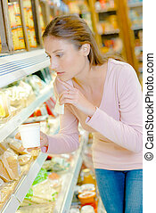 Woman contemplating at chilled counter
