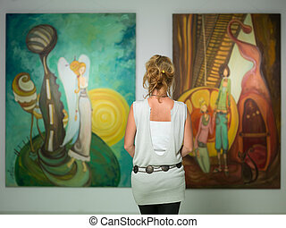 woman contemplating colorful paintings - rear view of younga...