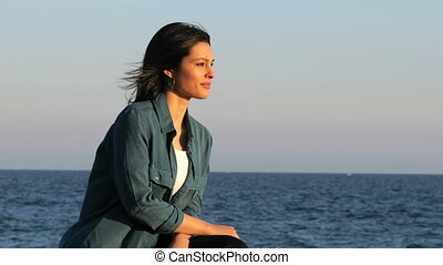 Woman contemplating ocean on the beach - Relaxed woman...