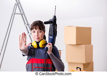 Woman contractor with hand drill at construction site