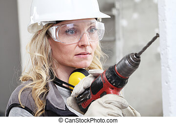 woman contruction worker using cordless drill driver making a hole in wall, builder with safety hard hat, hearing protection headphones, gloves and protective glasses, close up portrait