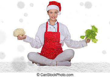 Woman cook in Santa hat, yoga, vegetables under snow on...