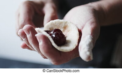 Woman cook manually sculpts dumplings stuffed with cherries...