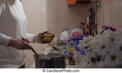 Woman cook Soup on the kitchen evening home interior
