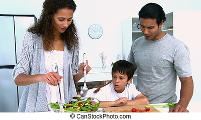 Woman cooking a salad with her son