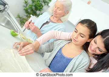 woman cooking a traditional apple pie with daughter and grandmother