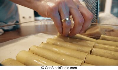 Woman cooking cannelloni Italian pasta at home, part of the...
