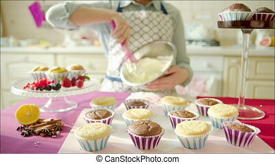 Woman cooking cup-cakes at home - Shot of tasty cup-cakes on...