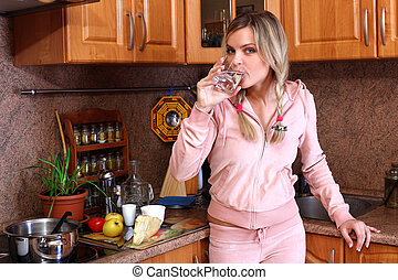 woman cooking dinner and drinking clear water in the kitchen