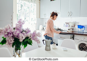 Woman cooking dinner and having coffee on the kitchen. Modern kitchen design.