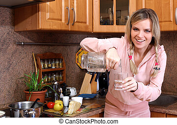 woman cooking dinner and holding glass with clear water in the kitchen