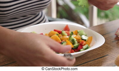 Woman cooking fresh vegetable salad with chopped cucumber red yellow tomatoes