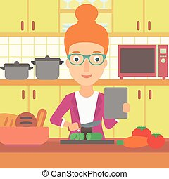 Woman cooking meal. - A woman holding a digital tablet and...
