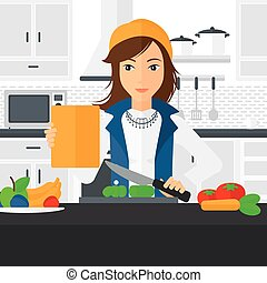 Woman cooking meal. - A woman standing in the kitchen with a...