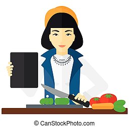 Woman cooking meal. - An asian woman holding a digital...