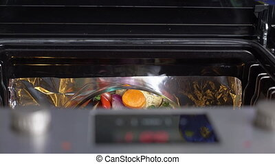 Woman cooking roasted vegetables in the oven closeup top view