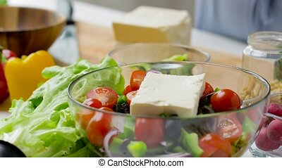 woman cooking vegetable salad with feta and oil - healthy ...