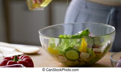 woman cooking vegetable salad with oil at home - healthy ...