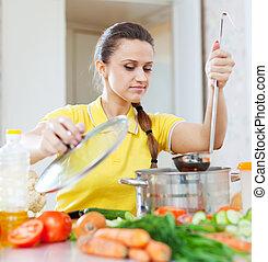 woman cooking vegetarian food in pan
