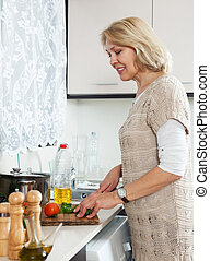 woman cooking vegetarian soup at home