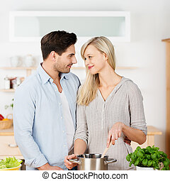Woman Cooking While Looking At Man In Kitchen