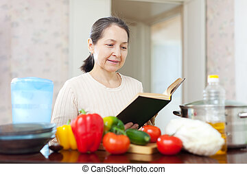 woman cooking with cookbook in kitchen at home