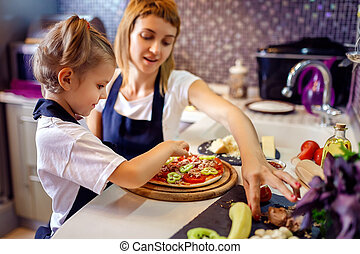 Woman cooking with little girl