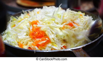 Woman cooks braised cabbage and carrots in the pan