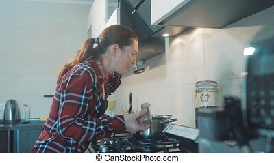 woman cooks soup pan food in the kitchen prevents the water...