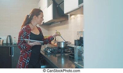 woman cooks soup pan in the kitchen prevents the water in...
