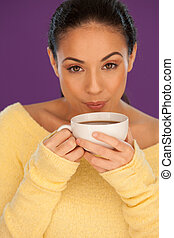 Beautiful brunette woman cooling down her coffee by gently blowing the surface beore she starts drinking it