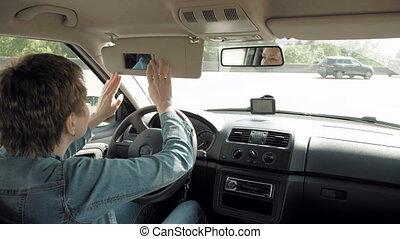 Woman corrects make-up in a car sun visor mirror