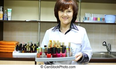 Woman-cosmetician represents nail polishes in salon