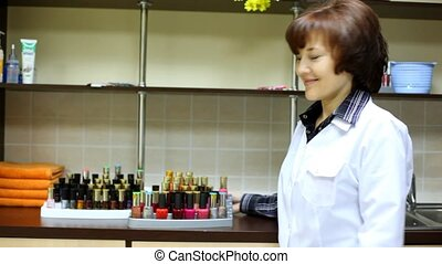 Woman-cosmetician represents nail polishes of different...