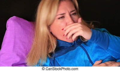 Woman coughing and resting in a bed