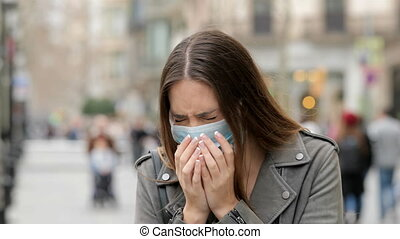 Woman coughing in the street with protective mask